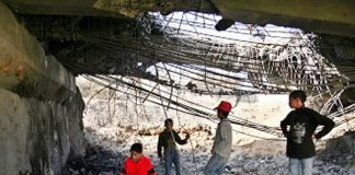 Palestinian children play under a huge hole in a bridge at Beit Hanoun in the Gaza Strip after it was blown up by an Israeli missile