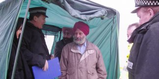 Duty Inspector Harrison tells Gate Gourmet TGWU branch secretary JARNAIL SINGH  that the tent must come down and the picket  on the hill must end