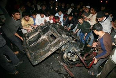 Palestinians remove a destroyed car hit by an Israeli aircraft in Rafah camp. Five adults and a child were murdered in the attack