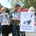 Relatives and widows of asbestos-related cancer victims outside the Houses of Parliament yesterday afternoon