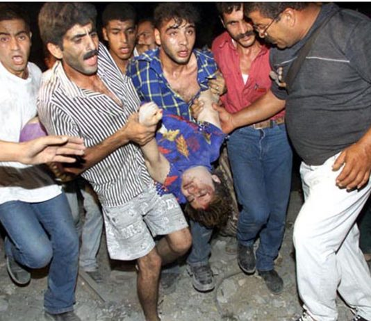 Palestinians carrying a badly injured  child as a result of an Israeli bombing of flats in Gaza