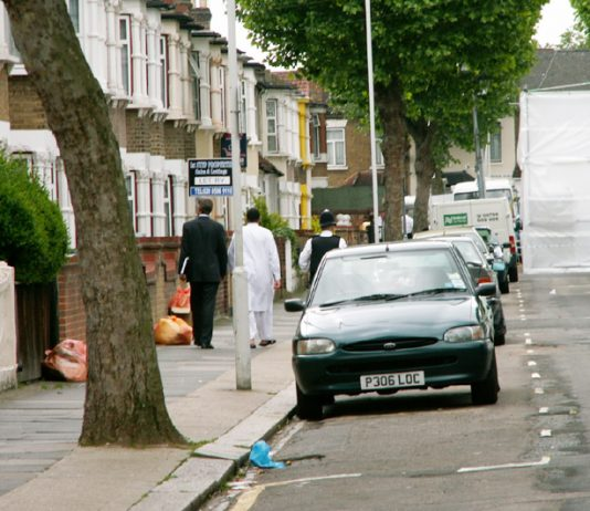 Police escort resident to his door in Lansdown Road, Forest Gate, yesterday midday, with number 46 hidden by plastic sheeting