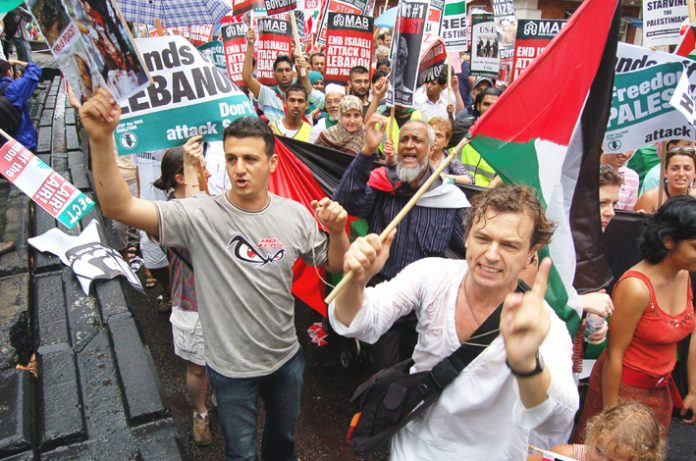 Demonstrators expressing their anger as they passed the US embassy in London on the 30,000-strong march demanding an end to the Israeli attack on the Lebanon