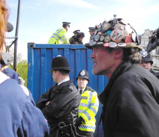 Police taking away the vast bulk of BRIAN HAW'S (right) posters and placards from Parliament Square in May last year