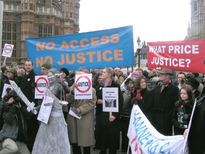 'Justice with her sword' stands blindfolded among a crowd of hundreds of legal aid lawyers outside parliament on Monday