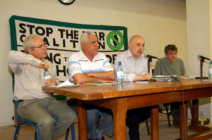 The platform at Wednesday night's meeting (left-right) SAMI RAMADANI, IFOU President HASSAN JUMAA AWAD AL-ASSADI, meeting chairman SABAH JAWAD and ANDREW BURGIN (Stop the War Coalition)