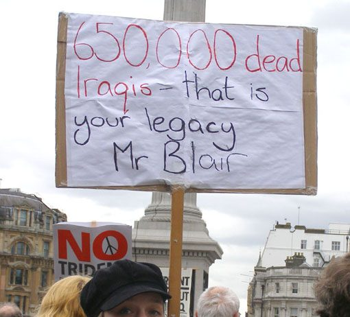 A demonstrator in London reminds Blair of the legacy that he brings as the new 'Middle East envoy'