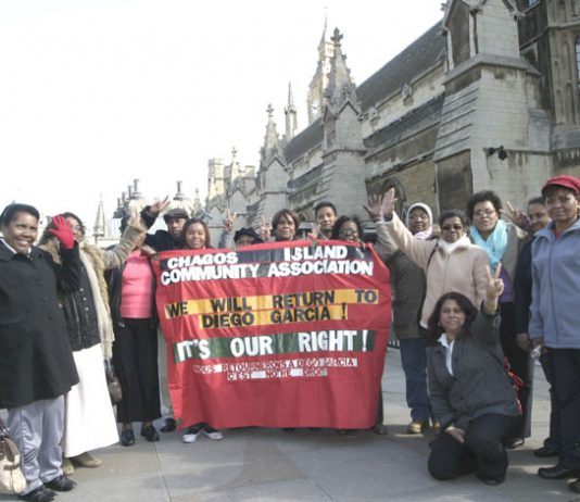 Chagossians with their Community Association banner, demanding the right to return to Diego Garcia, outside parliament yesterday