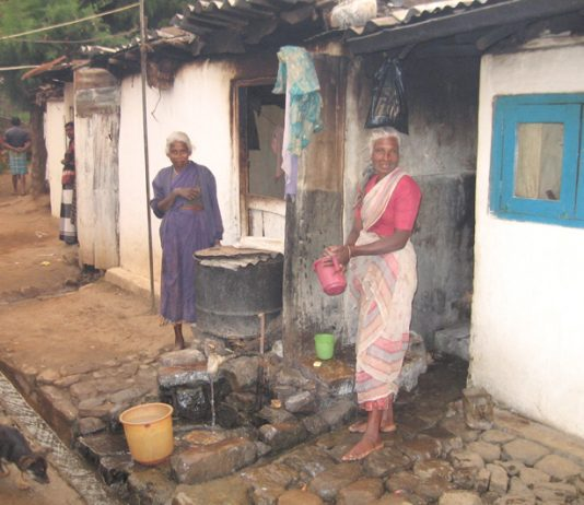 Sewage waste runs in the open drain – only feet away from where these Tamil plantation workers cook their food