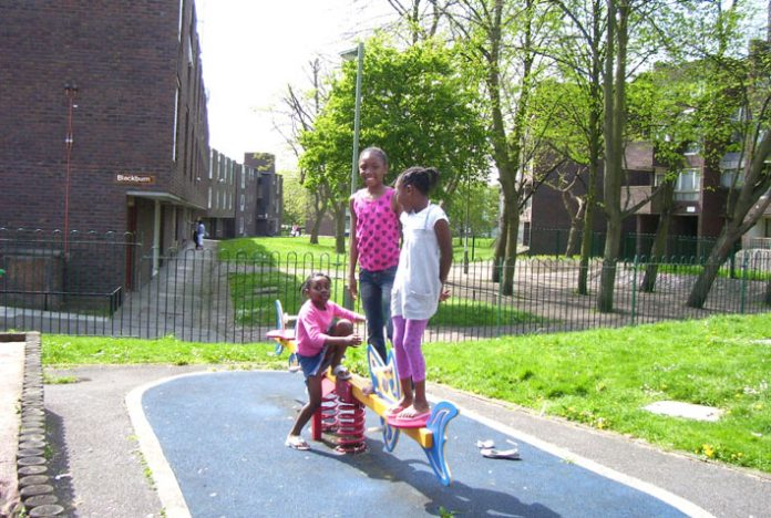 Children playing on the Grahame Park estate in front of the houses that are due to be demolished