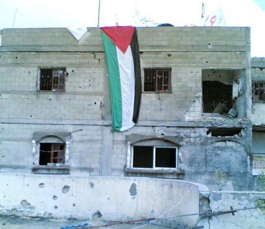 Palestinians fly their  flag in Beit Hanoun in defiance of Israeli army shelling of their homes