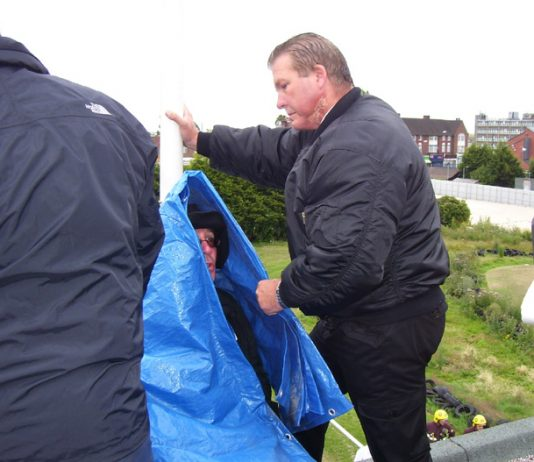 Council bailiffs wrap anti-academy protester HANK ROBERTS (who had D-locked himself on the roof) in a cover before using an angle grinder to release and evict him last Friday morning
