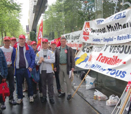 Peugeot workers lobby a shareholders meeting against factory closures in May 2006