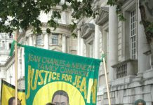 MARIA OTONE DE MENEZES (centre) holds a picture of her son Jean Charles De Menezes on a march to parliament