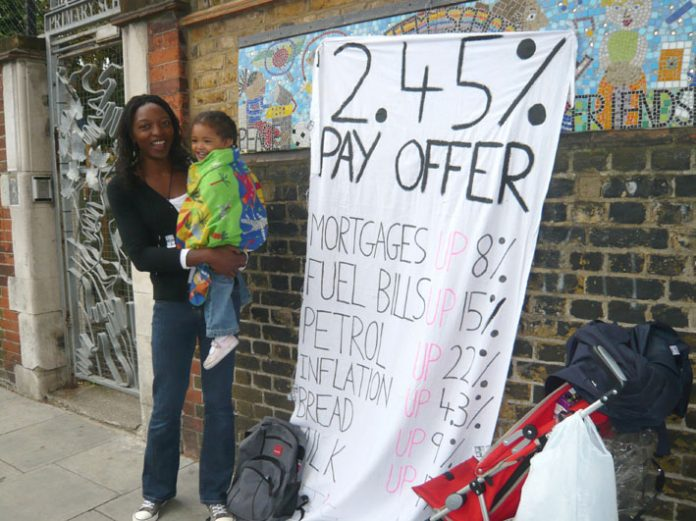 A school worker with her child during national strike action in July against a below-inflation pay deal