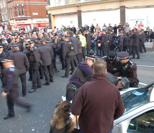 Police arresting a man during earlier protests outside the Israeli embassy against the bombing of Gaza