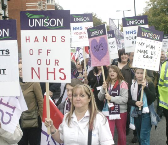 NHS workers marching in defence of the NHS stressing it is not about profit