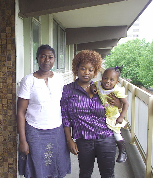 EVELYN, holding her daughter, with neighbour FELICIA on the Heygate estate