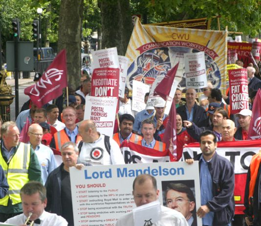 Postal workers marching along the embankment carrying a giant postcard to Business Secretary Mandelson demanding he stop destroying a great public service