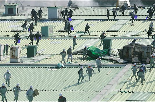 Korean SWAT police team members landed onto the roof of the Ssangyong assembly line building chase workers occupying the building in defence of their jobs
