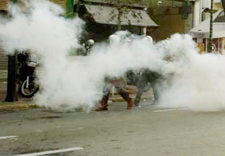 Greek riot police opening fire on the workers' demonstration with tear gas