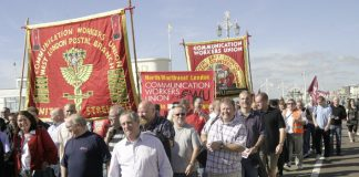Postal workers march outside the Labour Party Conference urging the government not to back the break up of the industry