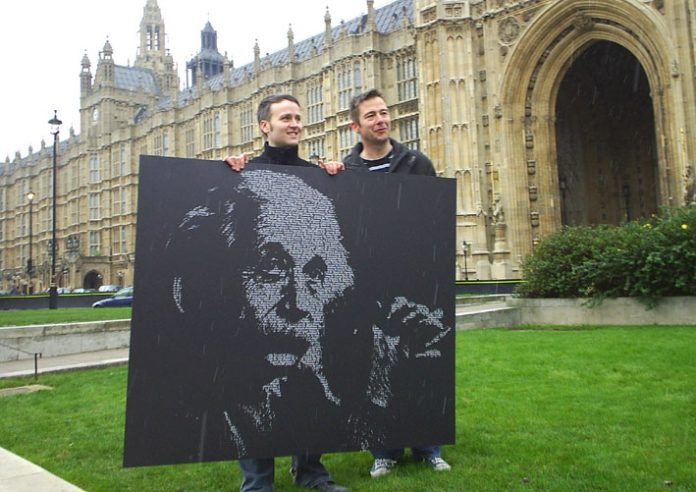 Two UCU members hold up a picture of Einstein outside the House of Commons on Wednesday Einstein who said about research 'If we knew what it was what we were doing, it would not be called research, would it?'