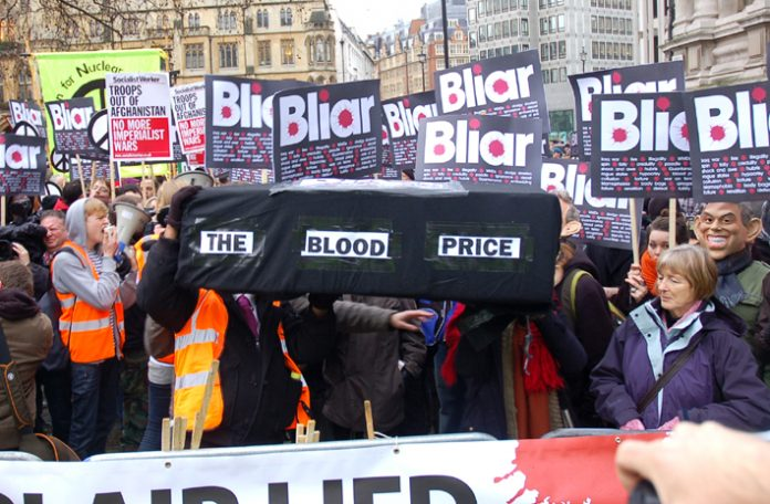 Demonstrators with a coffin illustrating the blood price of the Iraq war