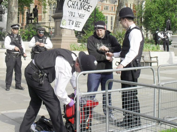 Armed police arrest and handcuff one of the peace protesters as they search his bag in Parliament Square yesterday morning