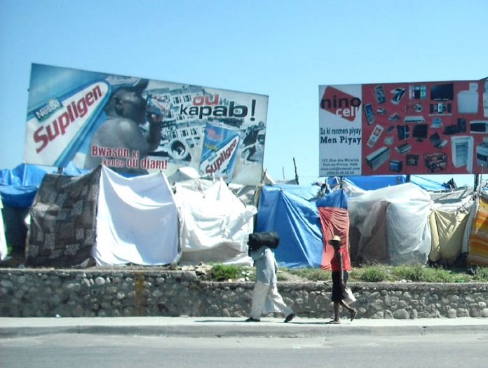 Haitians living in tents by the side of a main road