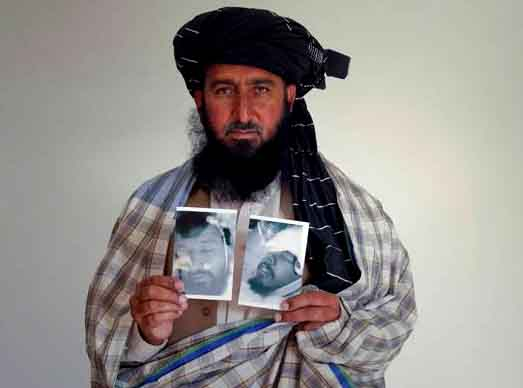 Kareem Khan holding up photographs of his brother and his son after they were killed
