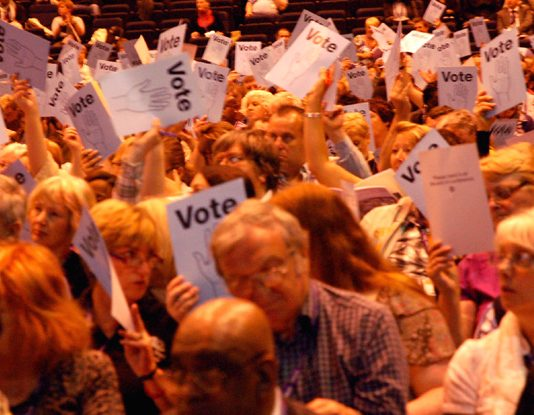 Unison conference delegates voting to oppose the coalition's attacks on health, education and pensions