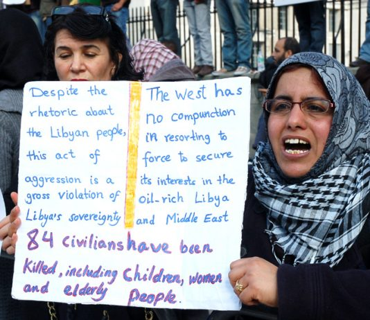 Woman holds her own detailed placard on a protest over the war on Libya earlier this year