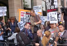 Demonstrators outside yesterday's hearings where MPs questioned the Murdochs and sacked police chiefs, demanding that Cameron and Murdoch go