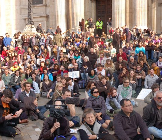 Hundreds of people listening to a speaker at the St Paul's camp