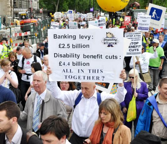 Disabled people and their supporters marching last May against benefit cuts