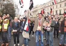 Syrians show their support for President Assad outside their embassy in London on March 17, the day after a terror bombing in Damascus killed 25