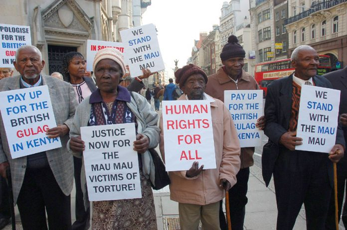 Mau Mau supporters outside the High Court demanding that the British government be held to account for mass murder in Kenya