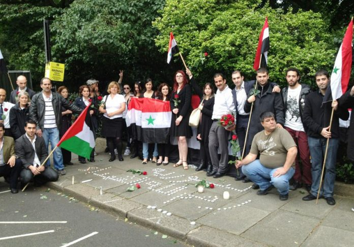 Syrians hold a vigil outside their embassy in London last Thursday to commemorate the Syrian government leaders who died in that day's terrorist bombing in Damascus