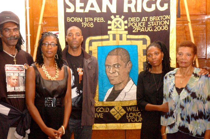 Marcia Rigg (2nd left) and Samantha Rigg-David (2nd right) with supporters and the Justice for Sean Rigg banner
