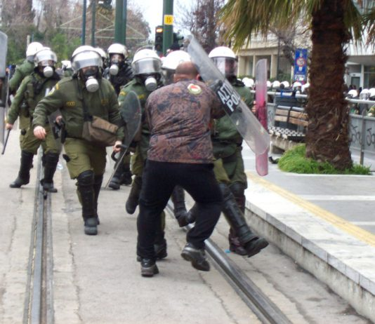 Greek worker stands his ground against an attack by riot police