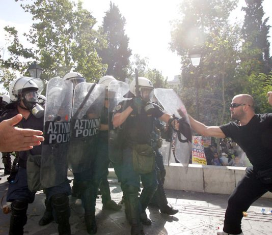 Greek worker takes on riot police during 120,000-strong march in Athens on Thursday's general strike