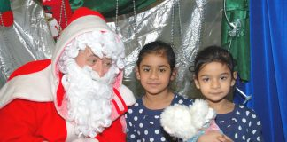 Father Chrismas with two young children at the Young Socialists Xmas Bazaar – many children will be going without this Christmas