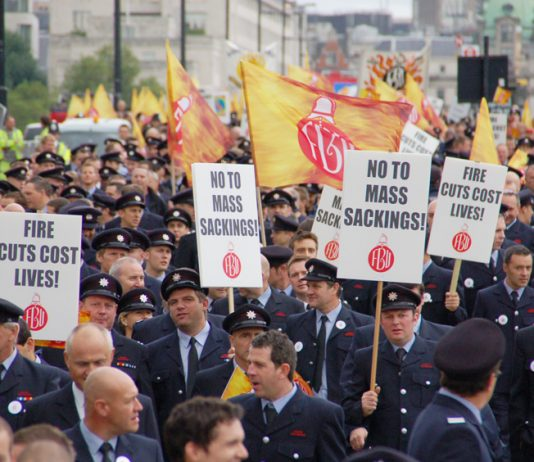 Firefighters marching in London with a current message that the fire service must be defended otherwise lives will be lost