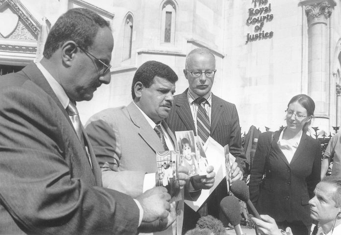 The father of Baha Mousa, the Iraqi hotel worker beaten to death by British troops holds photos of his son's family outside the High Court in London in July, 2004