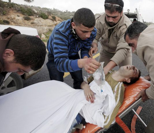 Young Palestinian injured after an attack by Israeli forces is treated for his injuries