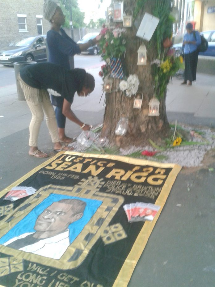 The banner of the Sean Rigg Justice and Change Campaign under a memorial to him outside Brixton Police station