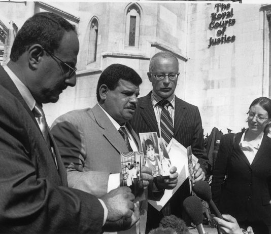 PHIL SHINER of Public Interest Lawyers outside the High Court, standing behind DAOUD MOUSA, seen holding pictures of his son, Baha and his family. Baha was beaten to death by British troops in Basra