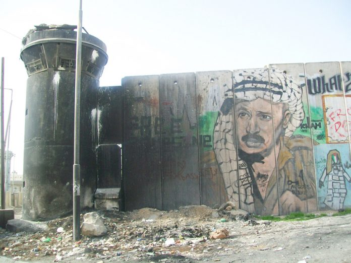 A picture of Yasser Arafat on the Israeli Separation Wall built so that Israel could annex settlements and surround Palestinian areas