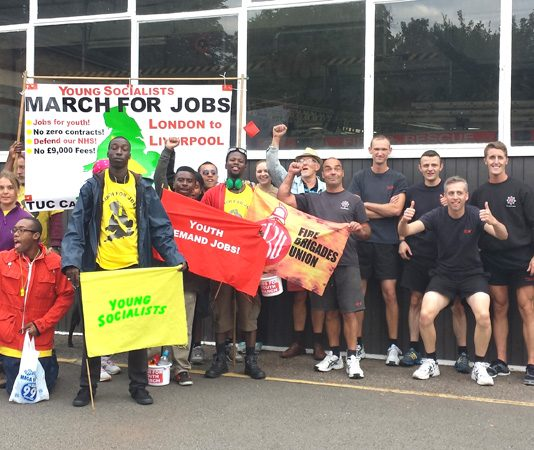 Firefighters greet the marchers at Studley Road Fire Station, Luton